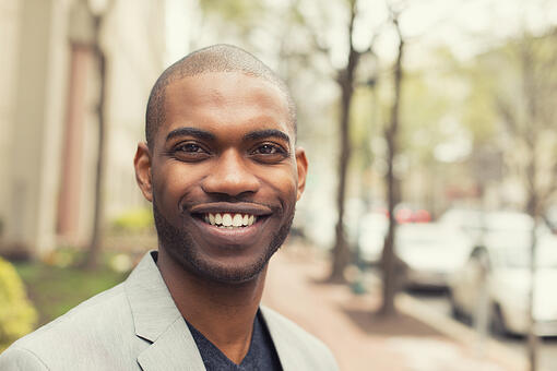Headshot portrait of young man smiling isolated on outside outdoors background.